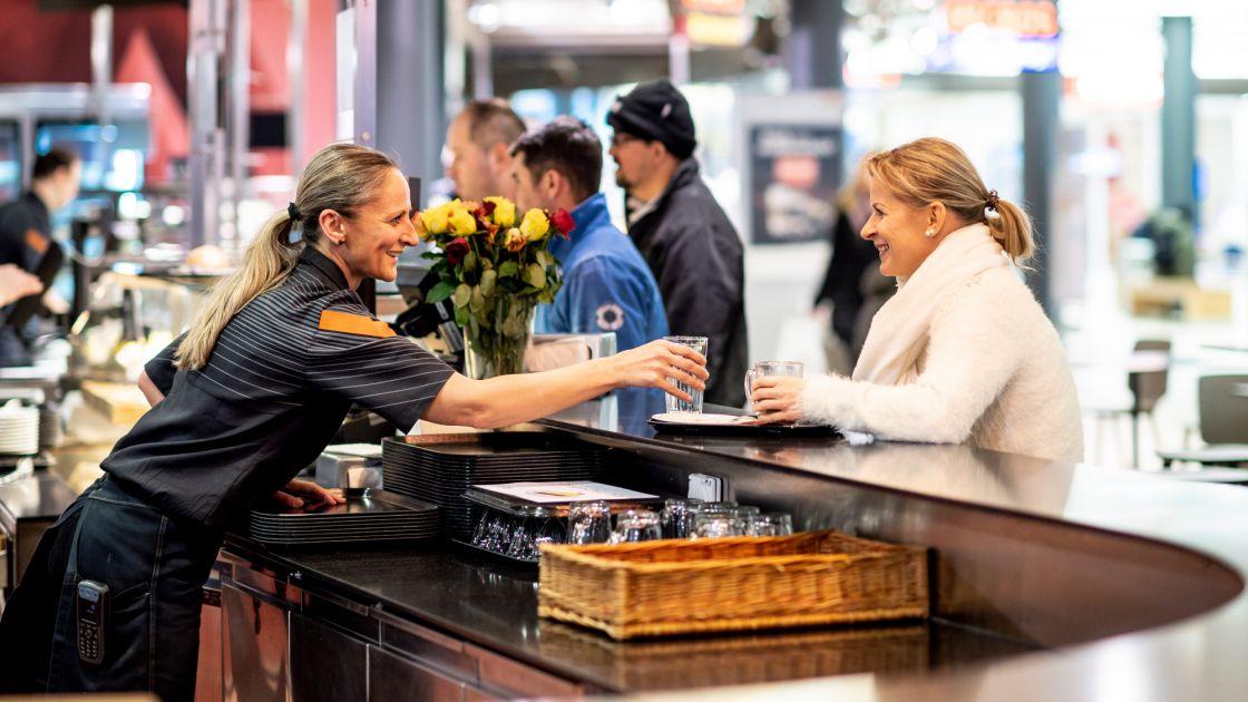 5d601749cd8cf5 Eine Mitarbeiterin von Migros-Gastro im Gespräch mit einer Kundin